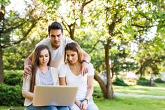 Amici di Amazig in natura che si siede sul banco e che per mezzo del computer portatile Fotografie Stock
