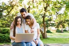 Amici di Amazig in natura che si siede sul banco e che per mezzo del computer portatile Fotografia Stock Libera da Diritti