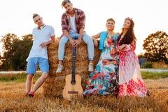 Amici di hippy con la chitarra in un giacimento di grano Fotografia Stock