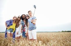 Amici di hippy con lo smartphone sul bastone del selfie Fotografia Stock