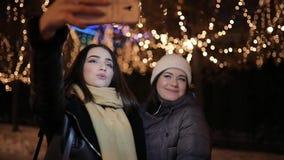 Amici di ragazze che fanno la foto del selfie al vicolo di notte decorato dalla ghirlanda stock footage