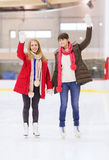 Amici di ragazze felici che ondeggiano le mani sulla pista di pattinaggio Fotografia Stock