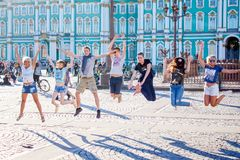 Amici di salto sul quadrato del palazzo del centro urbano fotografie stock libere da diritti