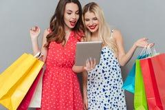 Amici di signore emozionali allegri con i sacchetti della spesa e la compressa Fotografia Stock Libera da Diritti