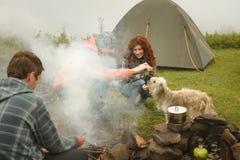 Amici divertendosi con il cane vicino al fuoco di accampamento Immagine Stock