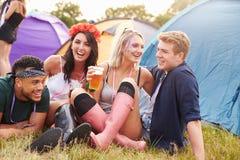 Amici divertendosi sul campeggio ad un festival di musica Fotografie Stock
