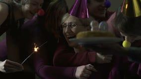 Amici e famiglia che abbracciano donna felice sulla sua festa di compleanno 80, celebrazione video d archivio