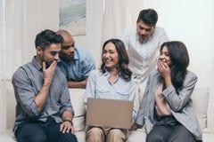 Amici emozionali che per mezzo del computer portatile mentre sedendosi sul sofà a casa Fotografia Stock
