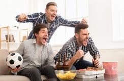 Amici emozionanti che guardano la partita e gridare di calcio immagini stock