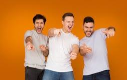 Amici emozionanti che indicano le dita alla macchina fotografica, fondo arancio immagine stock libera da diritti