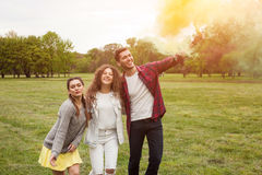 Amici emozionanti con fumo colorato nel parco Immagini Stock Libere da Diritti
