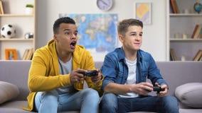 Amici europei e afroamericani emozionali che giocano i video giochi, tempo libero stock footage