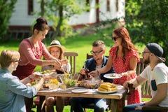 Amici felici cenando al ricevimento all'aperto di estate Fotografie Stock