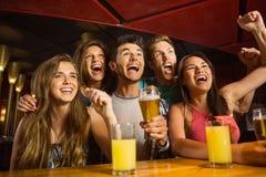 Amici felici che bevono birra e che incoraggiano insieme Fotografie Stock Libere da Diritti