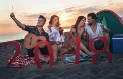 Amici felici che celebrano alla spiaggia il partito di vigilia del ` s da 2018 nuovi anni Fotografia Stock Libera da Diritti