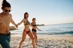 Amici felici che corrono lungo la riva di mare Fotografie Stock Libere da Diritti