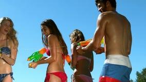 Amici felici che fanno battaglia della pistola a acqua video d archivio