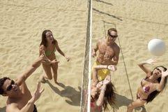 Amici felici che giocano pallavolo sulla spiaggia fotografia stock