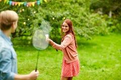 Amici felici che giocano volano al giardino di estate Fotografie Stock