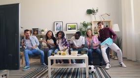 Amici felici che guardano gli sport a casa ballare e ridere celebrando vittoria archivi video