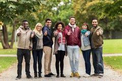 Amici felici che mostrano i pollici su al parco di autunno Fotografia Stock Libera da Diritti