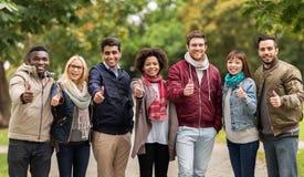 Amici felici che mostrano i pollici su al parco di autunno Fotografie Stock