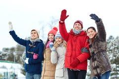 Amici felici che ondeggiano le mani sulla pista di pattinaggio sul ghiaccio all'aperto Fotografia Stock Libera da Diritti