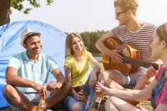Amici felici che riposano vicino al fiume Immagine Stock