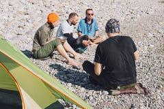 Amici felici che si accampano sulla spiaggia Fotografia Stock