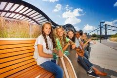 Amici felici che si siedono sul banco di legno in una fila Fotografia Stock