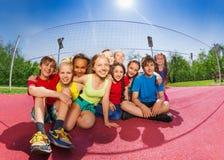 Amici felici che si siedono sulla corte del gioco di pallavolo Fotografia Stock