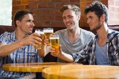 Amici felici che tostano con le pinte di birra Fotografia Stock