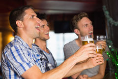 Amici felici che tostano con le pinte di birra il giorno dei patricks Immagine Stock Libera da Diritti