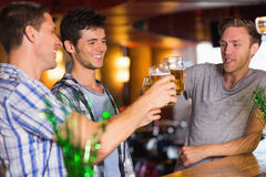 Amici felici che tostano con le pinte di birra il giorno dei patricks Fotografia Stock