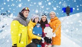 Amici felici con gli snowboard e lo smartphone Fotografia Stock Libera da Diritti