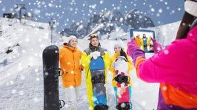 Amici felici con gli snowboard ed il pc della compressa Fotografia Stock