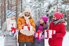 Amici felici con i contenitori di regalo nella foresta di inverno Fotografia Stock