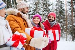 Amici felici con i contenitori di regalo nella foresta di inverno Fotografie Stock Libere da Diritti