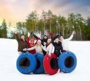 Amici felici con i tubi della neve all'aperto nell'inverno fotografia stock libera da diritti