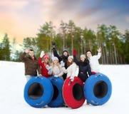 Amici felici con i tubi della neve all'aperto nell'inverno fotografie stock libere da diritti