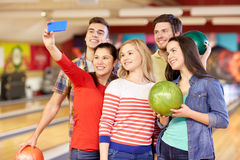 Amici felici con lo smartphone nel club di bowling Fotografia Stock Libera da Diritti