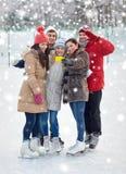 Amici felici con lo smartphone sulla pista di pattinaggio di pattinaggio su ghiaccio Fotografia Stock
