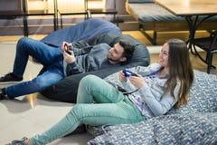 Amici felici delle coppie che giocano i video giochi con la leva di comando che si siede sulla sedia della borsa di fagiolo Fotografia Stock Libera da Diritti