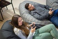 Amici felici delle coppie che giocano i video giochi con la leva di comando che si siede sulla sedia della borsa di fagiolo Fotografie Stock