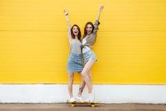 Amici felici delle donne che controllano parete gialla immagine stock