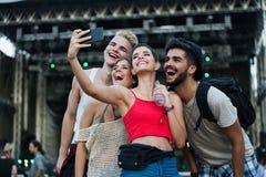 Amici felici divertendosi al festival di musica immagine stock
