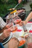 Amici felici divertendosi all'aperto, mani che tostano il vetro di vino rosato Fotografie Stock