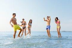 Amici felici divertendosi sulla spiaggia di estate Immagine Stock