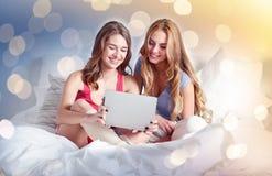 Amici felici o ragazze teenager con il pc della compressa a casa immagine stock