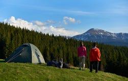 Amici femminili che fanno un'escursione insieme nelle montagne immagine stock